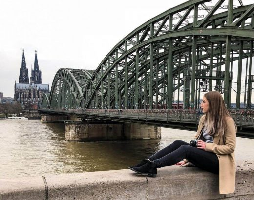 Verena sits looking out across the River Rhine, the Hohenzollern bridge is in the background